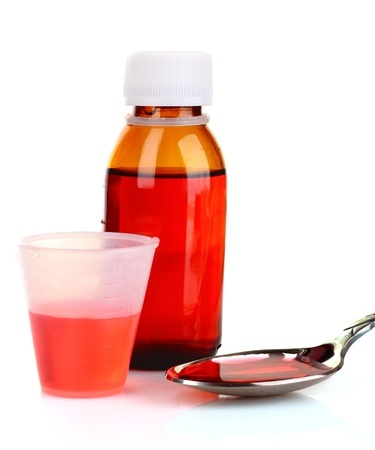 cough medicine bottle with poured dose on counter